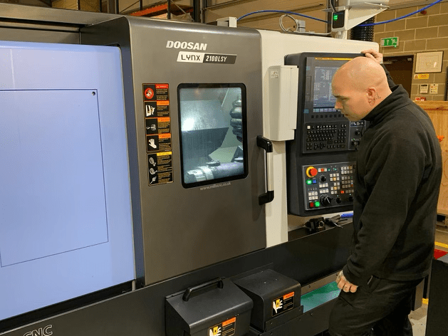 Machinist operating new CNC lathe recently arrived at Geosense