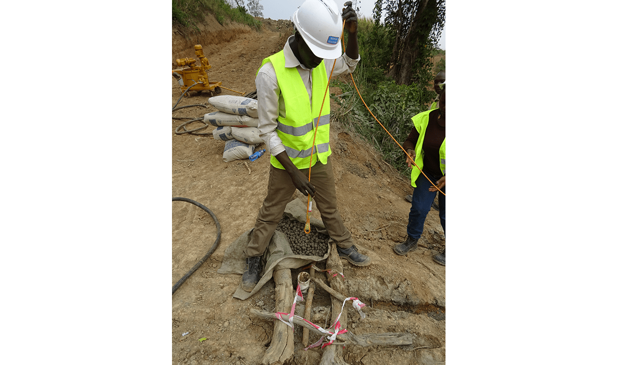 Engineer installing a vibrating wire piezometer at Kabaale Airport construction site