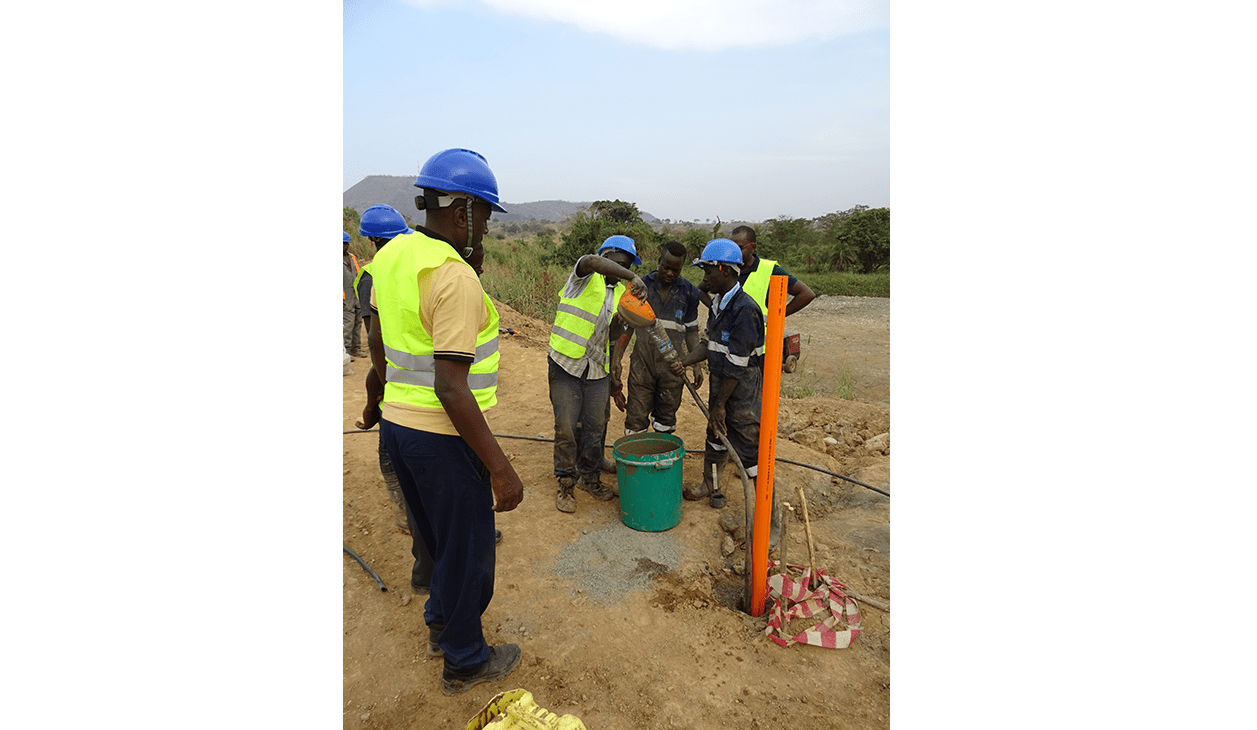 Team of Engineers placing grout around QJ inclinometer casing at Kabaale airport