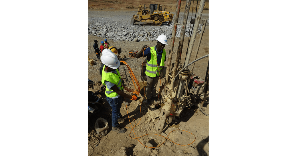 Drilling team installing vibrating a wire piezometer VWP-3000 at Kabaale airport