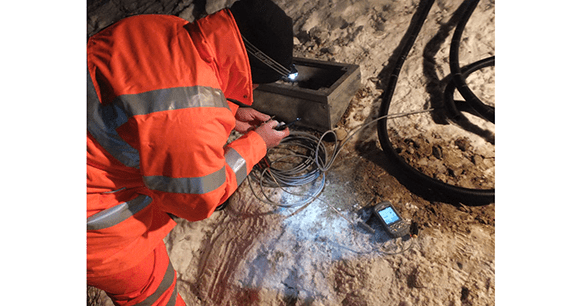 Engineer connecting cables of Geosense Track Monitoring System in Denmark at night in freezing conditions