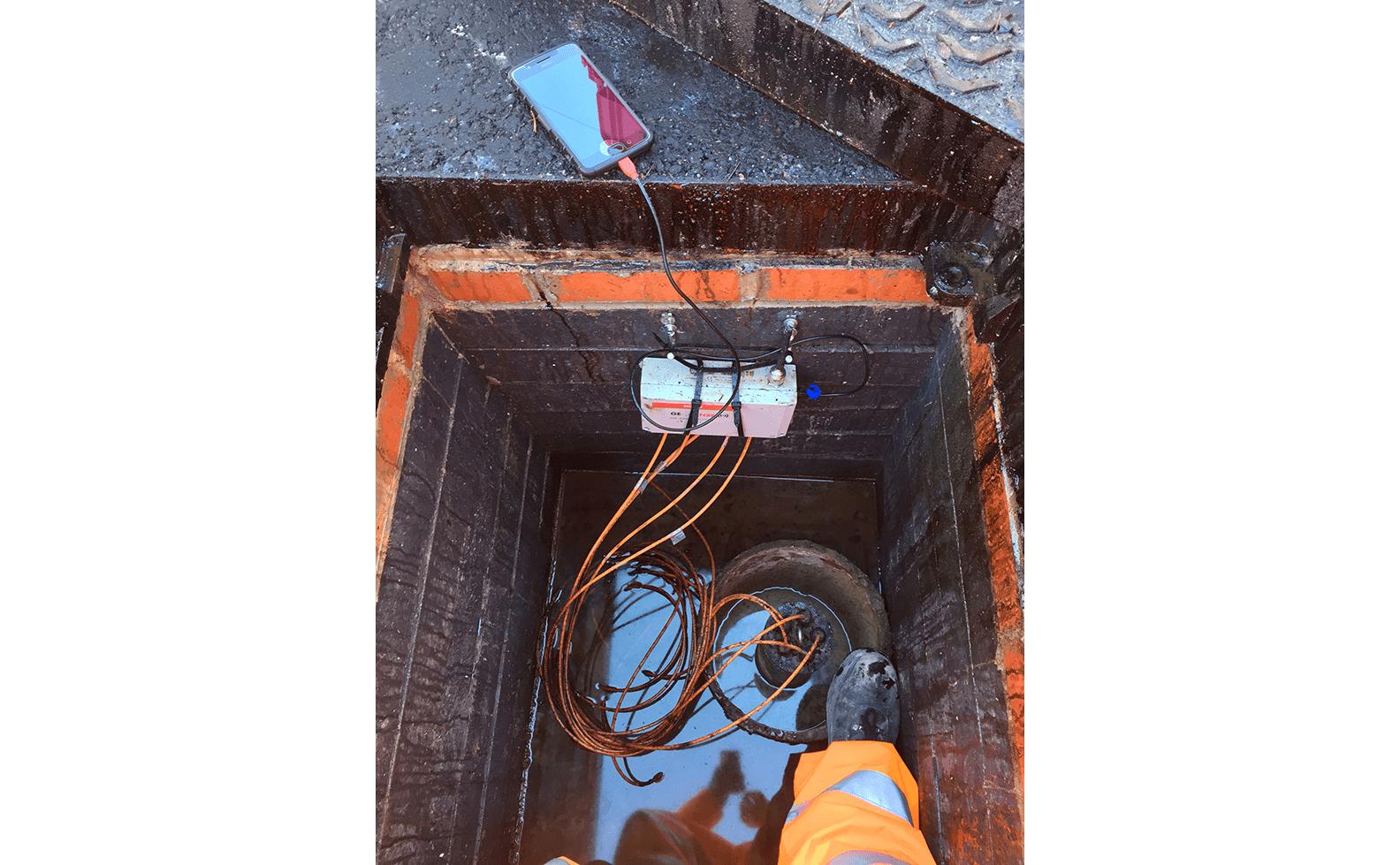 WI-SOS 480 Node mounted on side of brick manhole