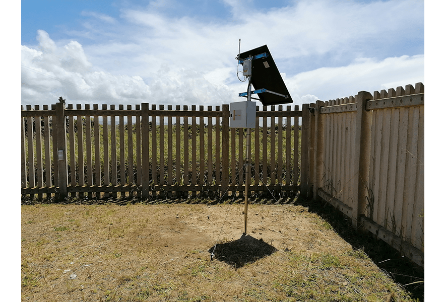 WI-SOS 480 Gateway with solar panel mounted on pole within wooden fence enclosure