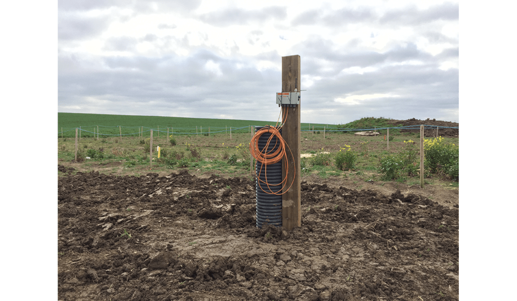 WI-SOS 480 five channel vibrating wire Node mounted on post next to borehole in a field