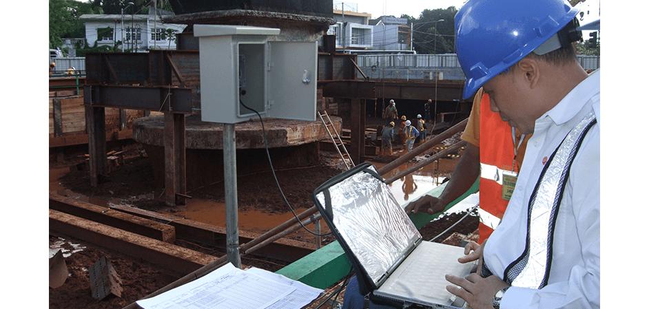 Engineer downloading data from Geosense strain gauges on Jakarta metro construction