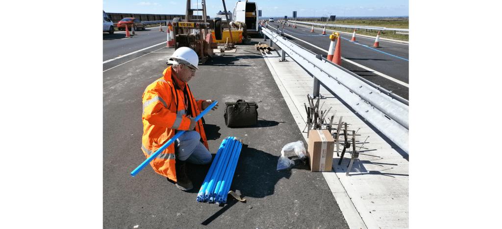 Engineer installing magnetic extensometers on road bridge deck