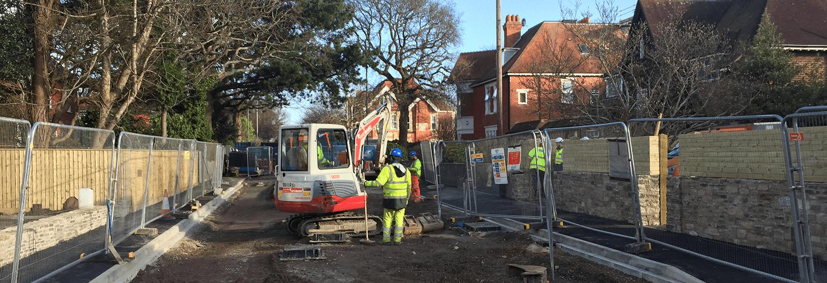 Mini excavator in road in suburban street
